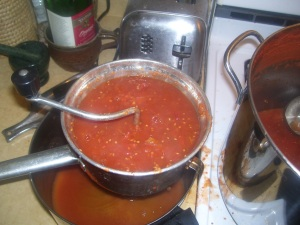 Straining tomatoes with hand strainer