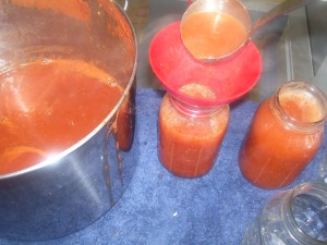 Pouring hot tomato sauce in sterilized canning jars